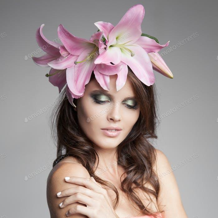 Schöne Frau mit Blumen Kranz in ihrem Haar. Rosa Lilie.