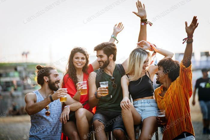 Group of young happy friends enjoying outdoor music festival
