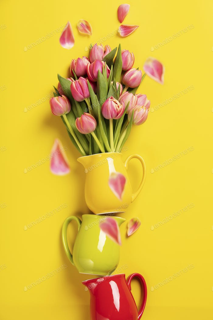 Perfect pink tulips in colorful jugs on yellow background