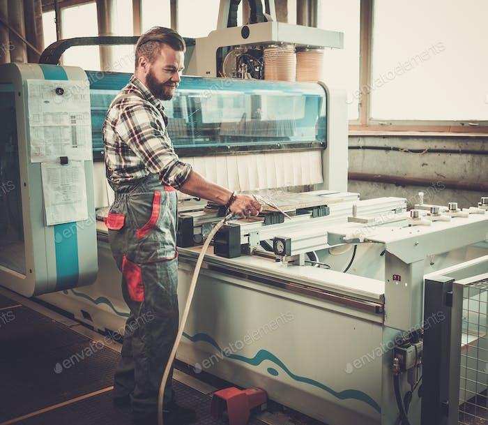 Плотник делает свою работу в столярной мастерской.
