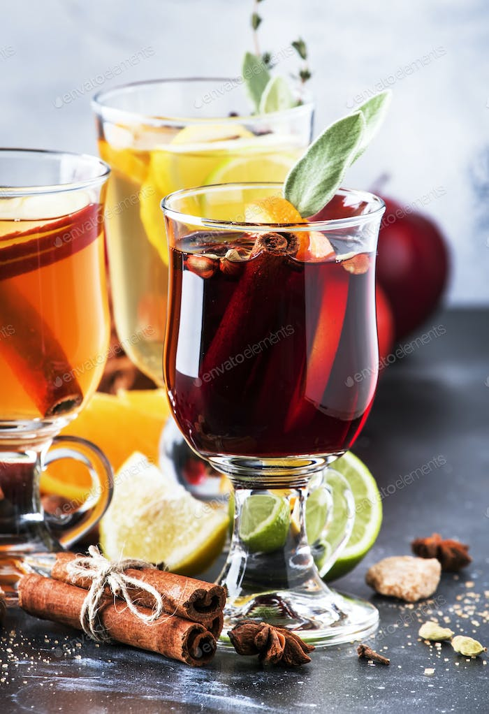 Mulled wine and mulled cider. Hot winter drinks and cocktails in glass mugs with spices and fruit