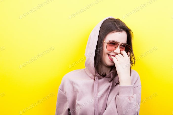Laughing cool hipster woman wearing a hood