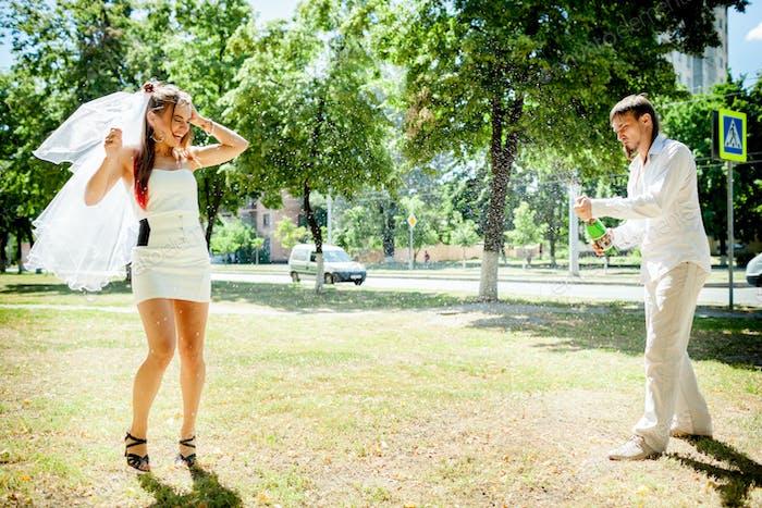Happy newlyweds celebrating wedding in park
