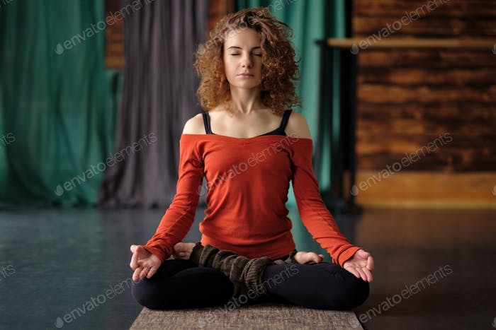 Yoga girl sitting in Lotus pose or Padmasana. Practicing on mat