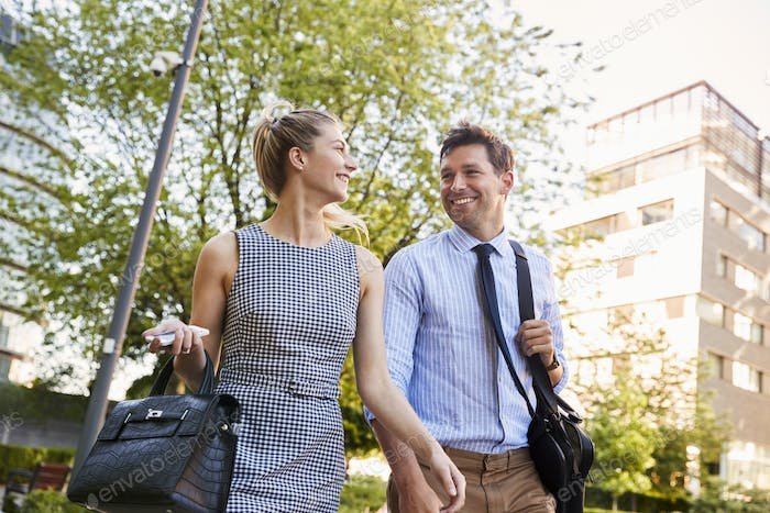 Businessman And Businesswoman Walk to Work Through City Park