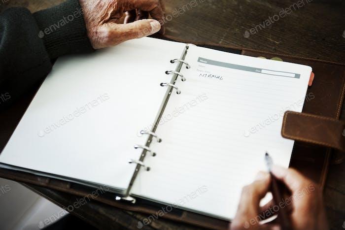 Senior person handwriting a journal
