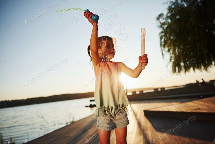Вечернее время. Счастливая маленькая девочка, играющая с пузырьками возле озера в парке