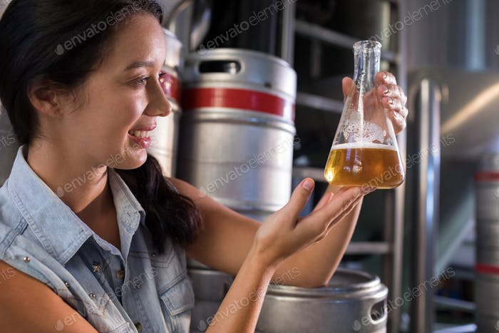 Smiling female worker examining beer at factory