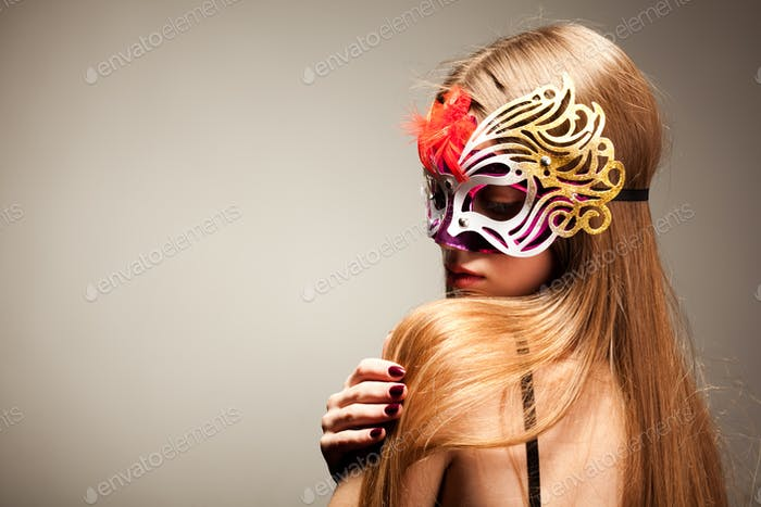 Woman in large multicolored carnival mask