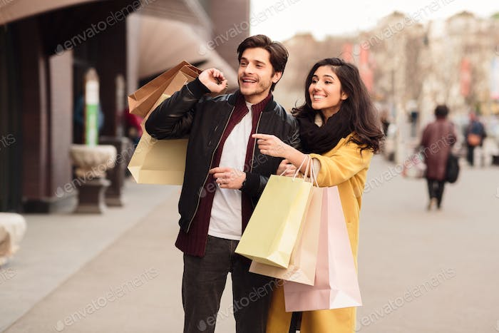Woman showing fashion store, walking with husband