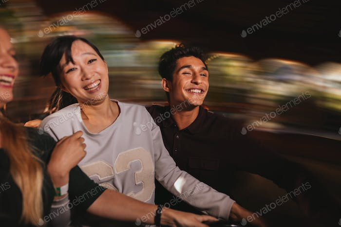 Three young people on amusement park ride.