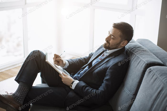 Man Working In Office Doing Notes