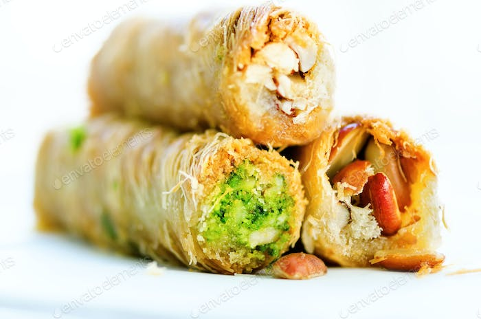 Turkish dessert - Baklava with peanut, pistachious, honey on white background. Healthy sweets. Copy