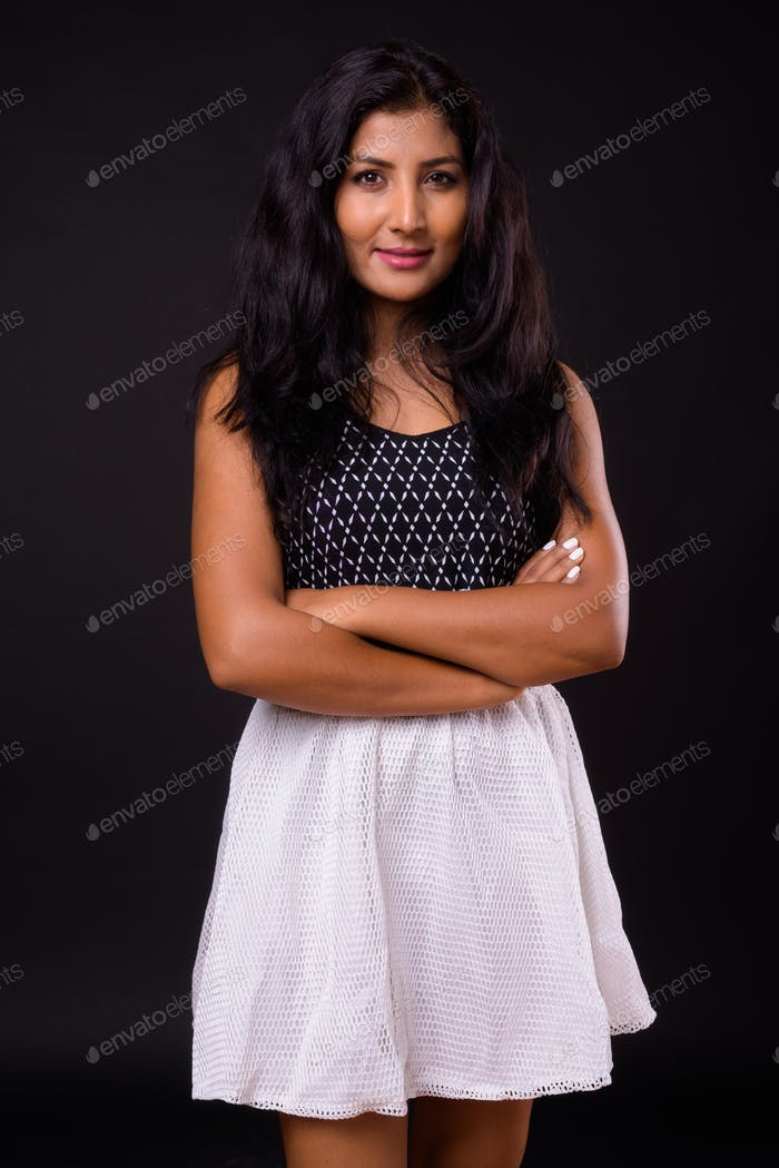 Portrait of young beautiful Indian woman with arms crossed