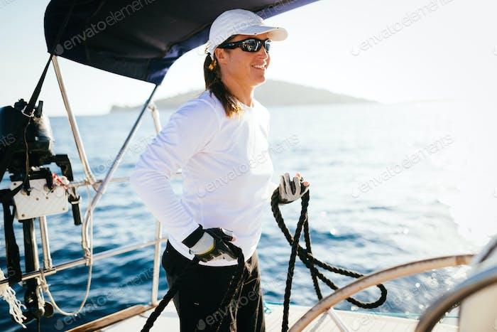 Attraktive starke Frau Segeln mit ihrem Boot