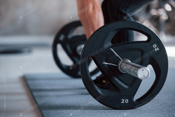 Lift with barbell. Cropped photo of woman doing squatting with barbell in the gym