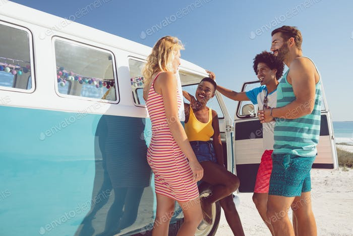 Happy diverse group of friends talking with each other near camper van at beach in the sunshine
