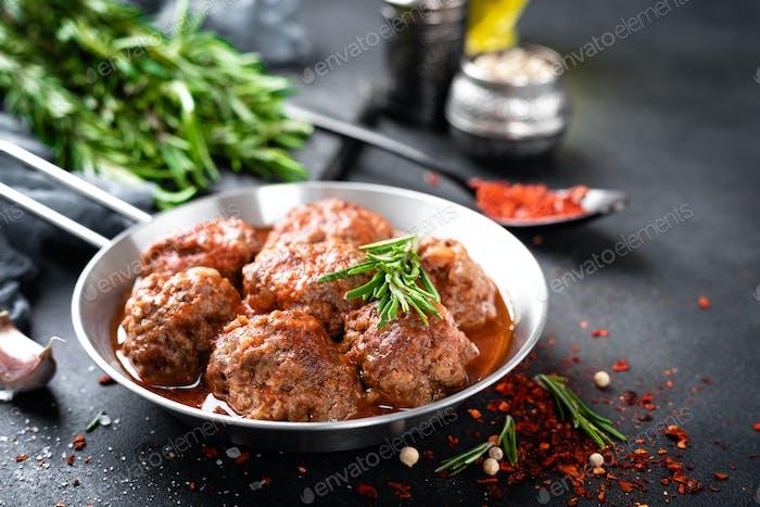 Rindfleischbällchen mit Gewürzen in Tomatensauce