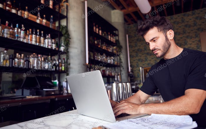 Male Owner Of Restaurant Bar Sitting At Counter Working On Laptop