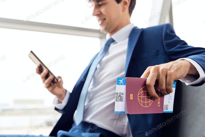 Businessman With Passport And Boarding Pass Sitting In Airport Departure Lounge Using Mobile Phone