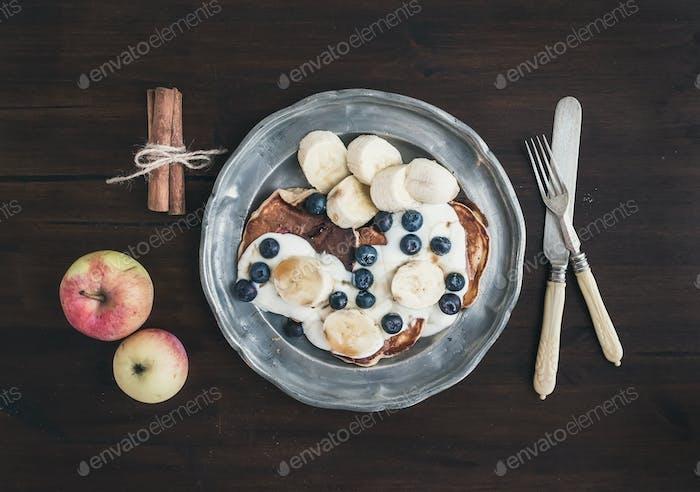 Breakfast set on dark wooden desk: apple and cinnamon pancakes w