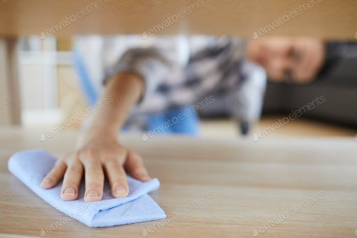 Woman wiping the dust in the room