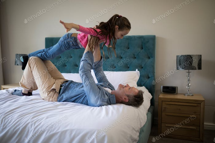 Happy father and daughter having fun on bed in bedroom