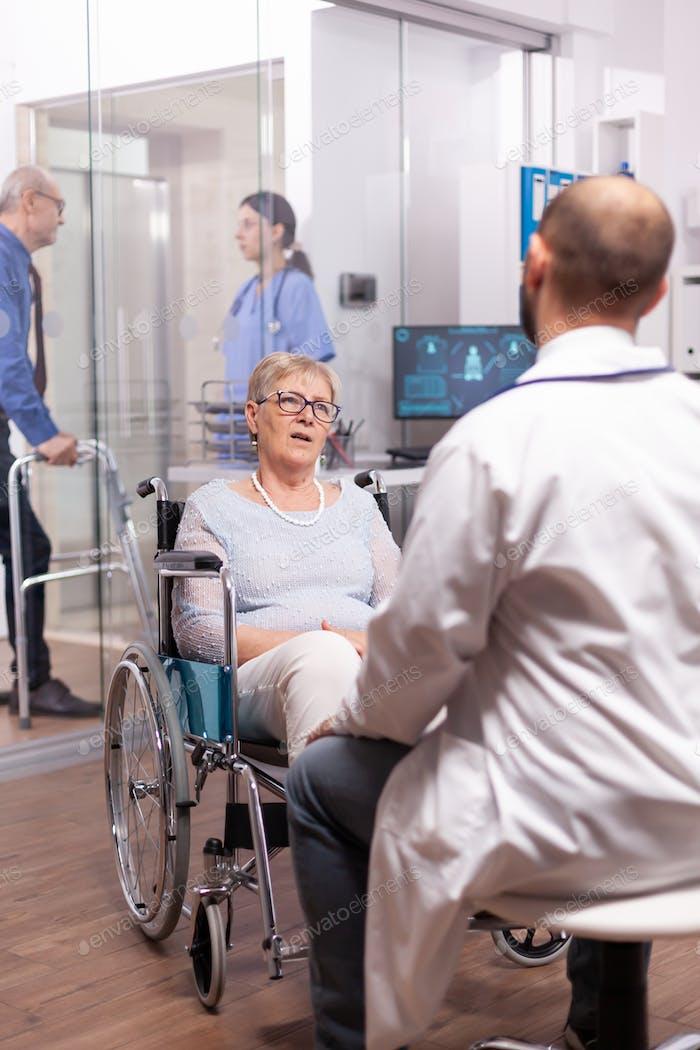 Gelähmtes Gespräch mit Geriaterin im Rollstuhl