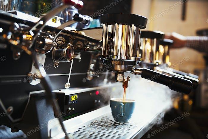 Spezialist Coffee-Shop. Eine Kaffeemaschine, die Kaffee macht. Dampf und Hitze.