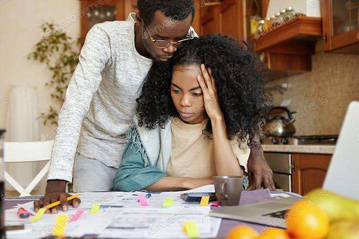 Konzept der Menschen, Finanzen und Wirtschaftskrise. Gestresstes junges dunkelhäutige Paar mit finanzieller PR