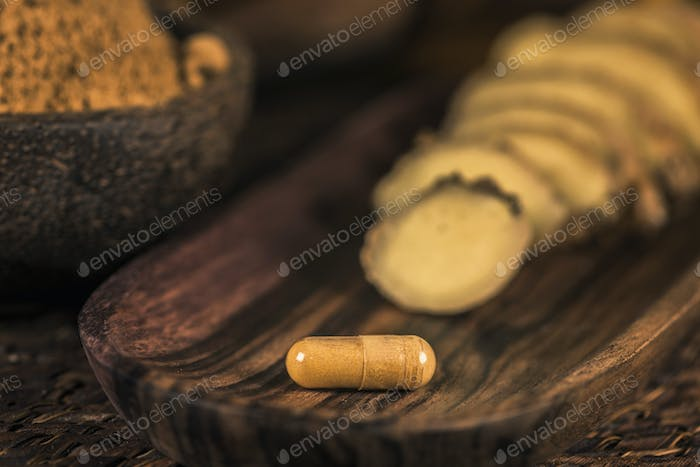 Ginger Herbal Supplement Capsule and Sliced Ginger Root
