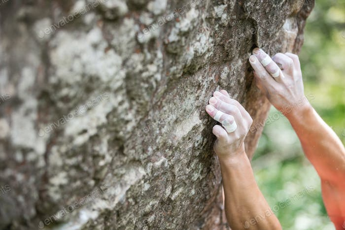 Rock climber's hands gripping small holds