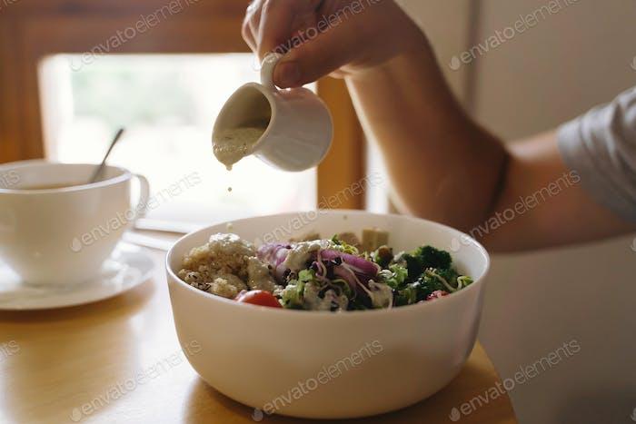 Mann gießt Sauce auf vegane Mahlzeit im Restaurant
