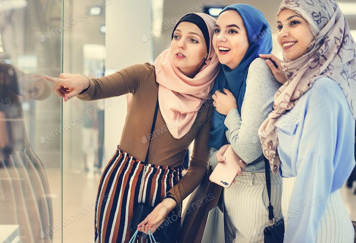 Islamic women friends shopping together at store