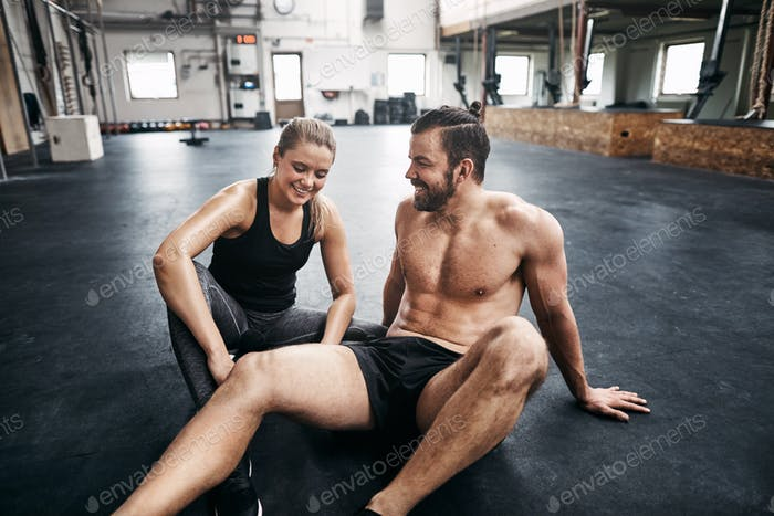 Two people resting resting on a gym floor after exercising
