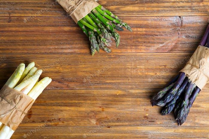 Homegrown frische natürliche Farbe organische Spargelspeere auf einem hölzernen Hintergrund. Ansicht von oben