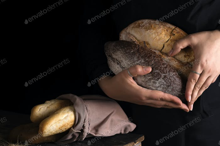 Close-up of woman hands as heart take fresh bread. Dark photo
