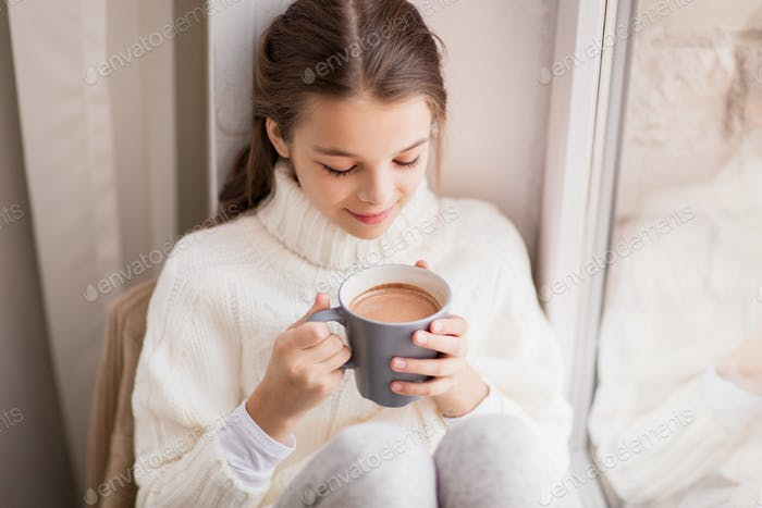 girl with cacao mug sitting at home window