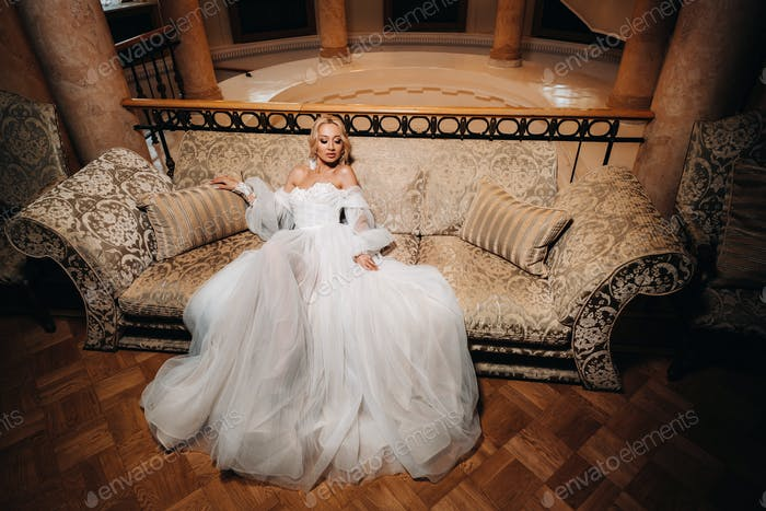 A beautiful bride is sitting on a luxurious sofa. Beautiful model girl in a white wedding dress