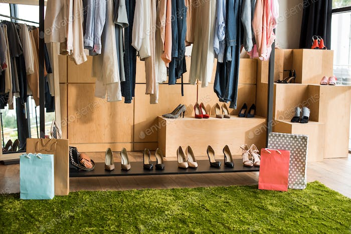 stylish clothes on hangers and fashionable shoes in boutique