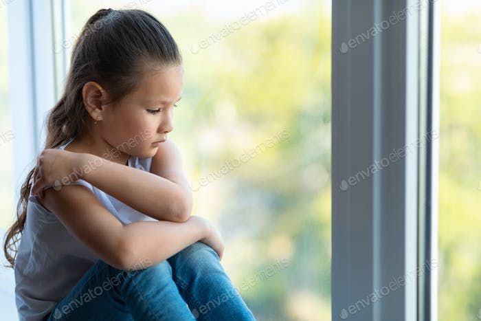 Unhappy Kid Girl Sitting Near Window Suffering From Loneliness Indoors