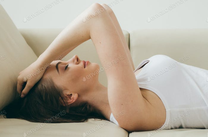A girl in despair cover her face with her hands sitting on a beige sofa. Beautiful girl close face
