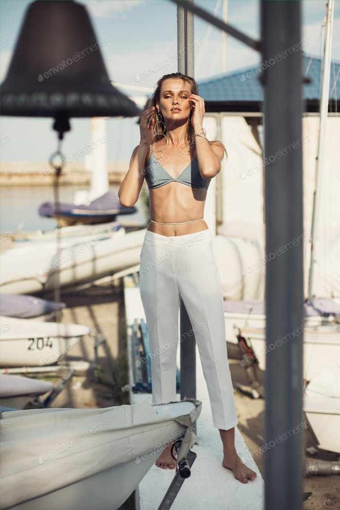 Sensual woman in swimsuit and white trousers in modern jewelry dreamily closing eyes among boats