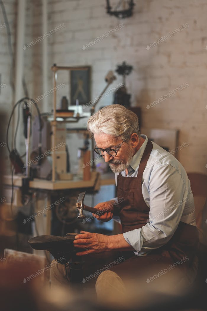 An elderly shoemaker in studio