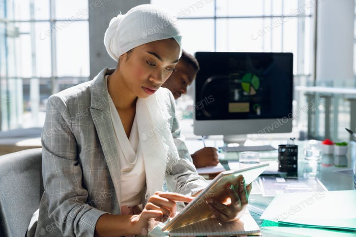 Businesswoman in hijab using digital tablet at desk