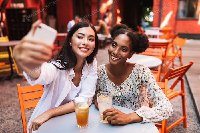 Two young ladies sitting at table with cocktails taking photos o