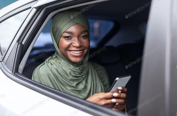 Smiling Black Muslim Woman Sitting On Back Seat In Car, Using Smartphone