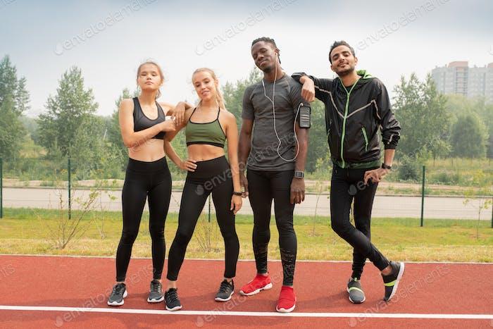 Vier junge interkulturelle Menschen in Sportbekleidung stehen auf der Rennstrecke