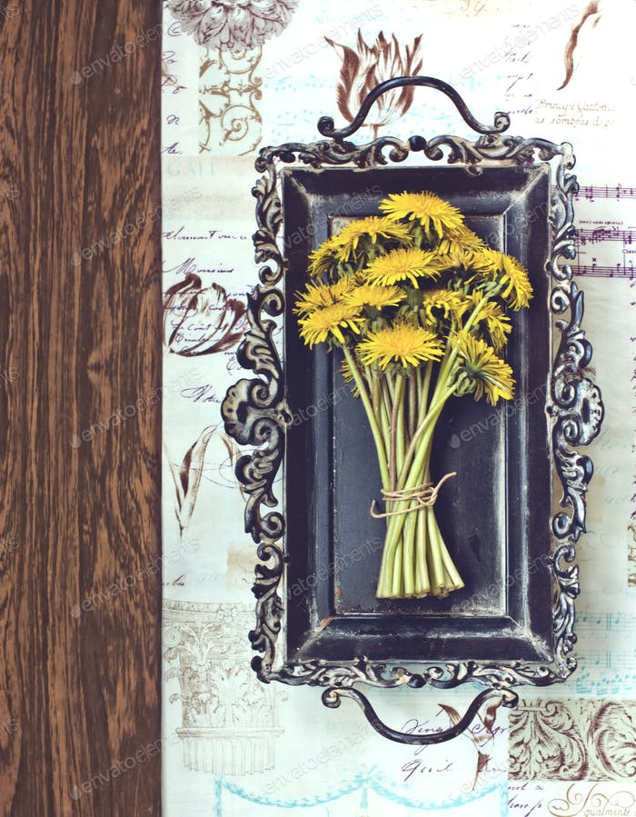 Dandelion on a tray with fabric and wooden textures