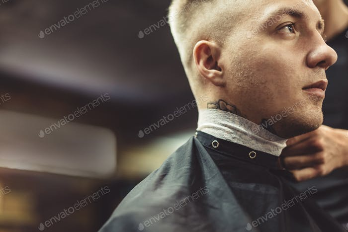 Anonymous barber preparing client